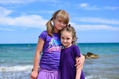 Twee kleine zusters die op het strand stellen Stock Foto's