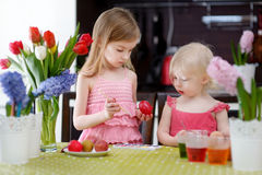 Twee kleine zusters die paaseieren schilderen Stock Foto