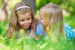 Twee kleine zusters die pret in de zomerpark hebben stock foto's