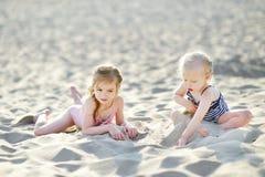 Twee kleine zusters die pret op een strand hebben royalty-vrije stock afbeelding