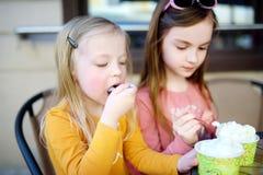 Twee kleine zusters die roomijs in een openluchtkoffie eten Royalty-vrije Stock Afbeeldingen