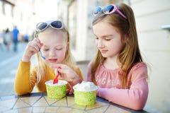 Twee kleine zusters die roomijs in een openluchtkoffie eten Stock Afbeelding