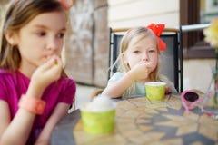 Twee kleine zusters die roomijs in een openluchtkoffie op de zomerdag eten Royalty-vrije Stock Fotografie