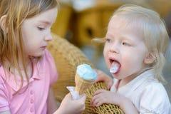 Twee kleine zusters die roomijs eten royalty-vrije stock afbeeldingen