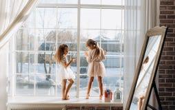 Twee kleine zusters kleedden zich buiten in de mooie kledingstribune op de vensterbank naast de spiegel de winter stock afbeelding