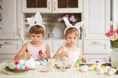 Twee kleine zusters met de oren van het witte konijn op hun hoofdenkleurstof de eieren voor de Pasen dienen in de comfortabele li royalty-vrije stock foto