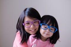 Twee kleine zusters met grote oogglazen royalty-vrije stock afbeelding