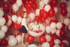Twee kleine zusters met rode en witte ballons Stock Foto