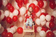 Twee kleine zusters met rode en witte ballons Royalty-vrije Stock Foto