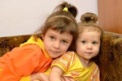 Twee kleine zusters zitten op een bank Portret Royalty-vrije Stock Foto's