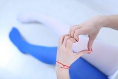 Twee kleurenkousen en een hart van handen Stock Afbeeldingen