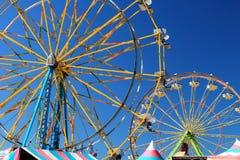 Twee kleurrijke die Reuzenraderen tegen een heldere blauwe hemel worden gesilhouetteerd royalty-vrije stock foto's