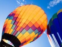 Twee kleurrijke hete luchtballons tegen blauwe hemel Stock Foto's