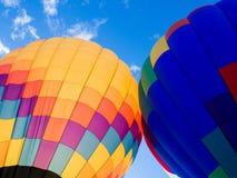 Twee kleurrijke hete luchtballons tegen blauwe hemel Stock Afbeeldingen