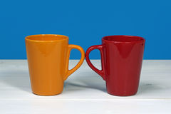 Twee kleurrijke koffiekoppen op witte houten lijst over blauwe backgro Royalty-vrije Stock Foto
