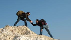 twee klimmers beklimmen achter elkaar op witte rots Groepswerk van bedrijfsmensen de toeristen geven hand aan elkaar stock footage