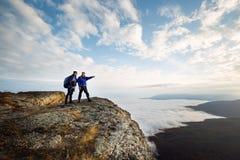 Twee klimmers die zich bovenop top boven wolken in de bergen bevinden Wandelaarmens die met zijn hand richten die route bespreken Stock Fotografie