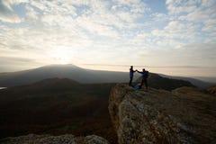 Twee klimmers die zich op top boven wolken in de bergen bevinden die handen houden Silhouetten van wandelaars die stijgen vieren Royalty-vrije Stock Fotografie