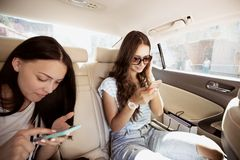 Twee knappe donker-haired meisjes, gekleed in toevallige stijl, zitten in de achterbank van een luim en een tekst op hun stock afbeelding