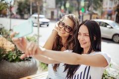Twee knappe dunne meisjes met lang donker haar, gekleed in toevallige gerstkorrel, zitten bij de bank en nemen een selfie, royalty-vrije stock afbeeldingen