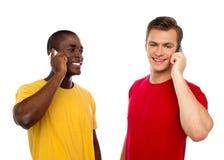 Twee knappe mensen die op cellphone communiceren Stock Afbeelding