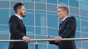 Twee knappe slimme bedrijfsmensen die een gesprek op terras van de bureaubouw hebben stock footage