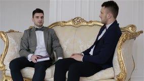 Twee knappe zakenlieden die in kostuums op een bank zitten die zaken bespreken stock video