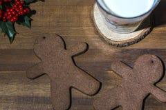 Twee koekjes van de peperkoekmens met een glas melk op een houten backgroun, sluiten omhoog stock afbeelding