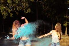 Twee koele jonge vrouwenvrienden die pret met het exploderen Holi hebben powd Stock Fotografie