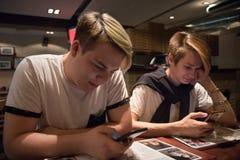 Twee in koffie zitten en vrienden die smartphones letten op Heb online pret royalty-vrije stock fotografie