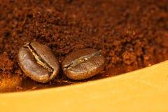 Twee koffiebonen en grondkoffie Stock Foto's