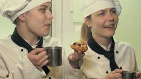 Twee kokvrouwen die pret in een keuken hebben stock videobeelden