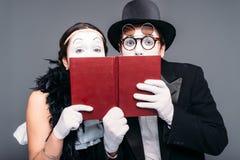 Twee komedieuitvoerders die met boek stellen stock fotografie