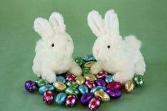 Twee konijntjes met miniatuurchocoladeeieren. Stock Afbeelding