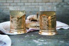Twee kop theeën in glazen met kophouders en cakes stock foto's