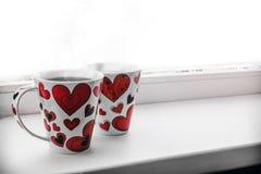 Twee koppen met hete die koffie of thee samen met harten op wh worden geïsoleerd Stock Afbeelding