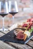 Twee koppen met rode geroosterde wijn en ruw rundvleeslapje vlees op leiraad royalty-vrije stock afbeeldingen