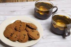 Twee koppen van groene thee en een kom van de koekjes van chocospaanders stock foto