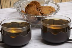 Twee koppen van groene thee en een kom van de koekjes van chocospaanders royalty-vrije stock foto's