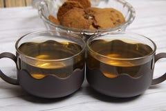 Twee koppen van groene thee en een kom van de koekjes van chocospaanders stock afbeeldingen