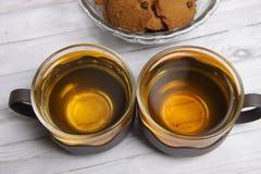 Twee koppen van groene thee en een kom van de koekjes van chocospaanders stock foto's