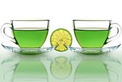 Twee koppen van groene thee met citroen op een witte achtergrond Stock Foto