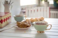 Twee koppen van hete thee met twee cakes op een witte lijst Stock Foto