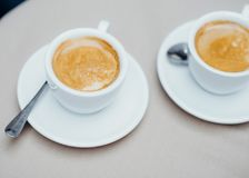 Twee koppen van koffie bij de lichte lijst Stock Afbeelding