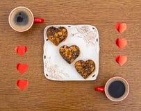 Twee koppen van koffie, een plaat met Valentijnskaartendag hart-vormige cakes en rood horen Stock Afbeeldingen