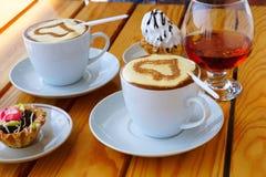 Twee koppen van koffie, een wijnglas brandewijn en cake stock foto