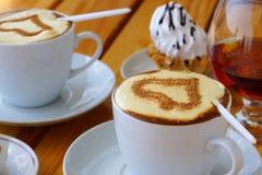 Twee koppen van koffie, een wijnglas brandewijn en cake stock afbeelding