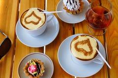 Twee koppen van koffie, een wijnglas brandewijn en cake royalty-vrije stock foto