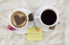 Twee koppen van koffie en een de stickergroet van de valentijnskaartdag stock afbeeldingen