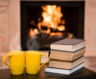 Twee koppen van koffie met boeken op de achtergrond van de open haard Royalty-vrije Stock Afbeelding
